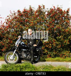 Homme plus âgé en cuir sur une moto Banque D'Images