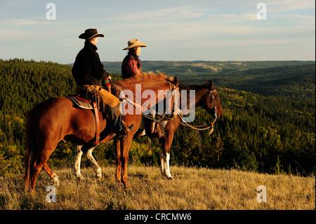Cowboy et cowgirl assis à cheval, à la recherche dans la distance, de la Saskatchewan, au Canada, en Amérique du Banque D'Images