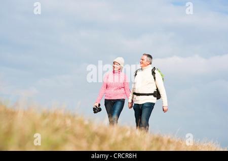 Couple marche main dans la main dans la région de Meadow Banque D'Images