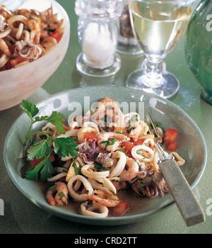 Une salade de fruits de mer, les calmars, les crevettes et les moules à la tomate et aux herbes, recette Italie, Banque D'Images