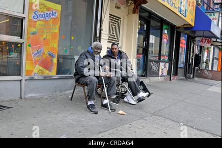 Pauer assis sur le trottoir à Harlem, USA, New York, Manhattan Banque D'Images