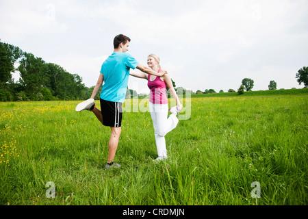 Jeune couple faisant des exercices d'étirement dans un pré Banque D'Images