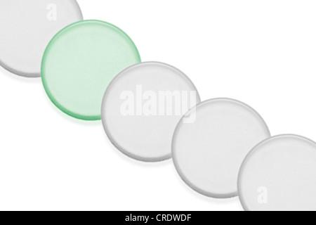 Comprimés blancs dans une rangée avec un comprimé vert Banque D'Images