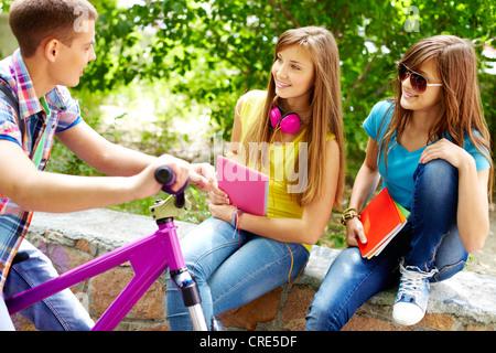 Guy sur un vélo à traîner avec ses amis de l'école Banque D'Images