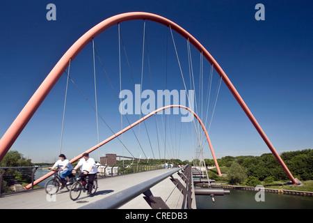Les cyclistes sur le pont en arc en acier rouge sur le Rhine-Herne-canal au parc Nordstern, Allemagne, Rhénanie Banque D'Images