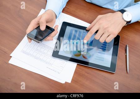 Jeune homme d'affaires travaillant avec des appareils modernes. Banque D'Images