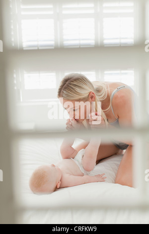 Mère embrassant les pieds de bébés on bed Banque D'Images
