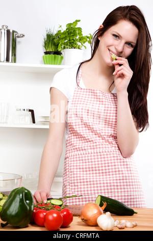 Happy young woman in a Kitchen grignoter une salade concombre alors que pour hacher Banque D'Images