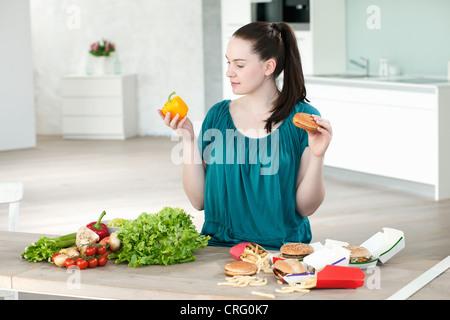 Femme avec restauration rapide et légumes Banque D'Images