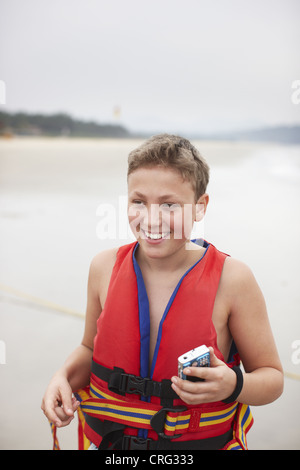 Teenage boy wearing gilet on beach Banque D'Images