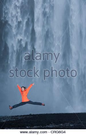 Randonneur sauter de joie en cascade Banque D'Images