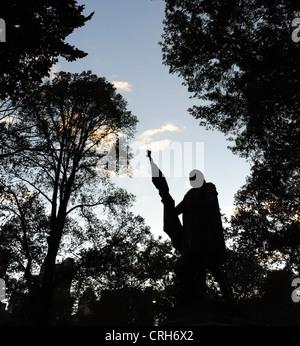 Ciel bleu soir vue silhouette sculpture de Christophe Colomb, avant de l'arbre en automne, le Mall, Central Park Banque D'Images