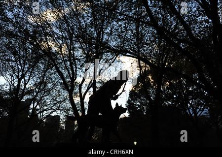 Lumière du soir sur silhouette sculpture indienne Hunter, debout devant les arbres d'automne, Central Park South, Banque D'Images