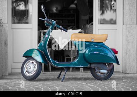 Éclaboussé de couleur bleu nostalgique Scooter stationné à l'extérieur d'un restaurant italien Banque D'Images