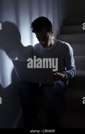Teenage male en utilisant son ordinateur portable, assis dans l'escalier sombre..