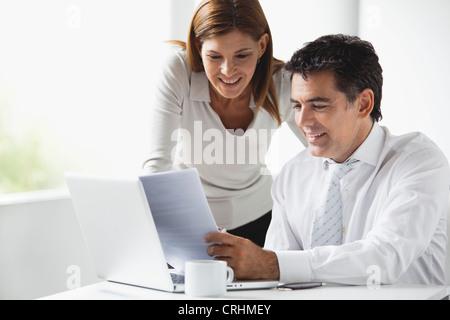 Des collègues d'affaires looking at laptop computer together Banque D'Images