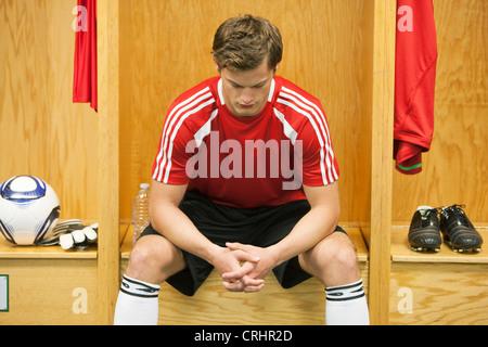 Joueur de foot assis seul dans la salle de casier
