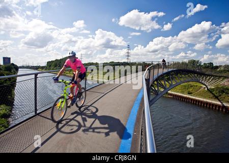 Biker sur un pont au-dessus du canal Rhin Herne, Rhein-Herne-Kanal, dans Ripshorst avec gazomètre Oberhausen en Banque D'Images