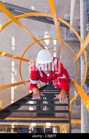 Worker climbing ladder à la raffinerie de pétrole Banque D'Images
