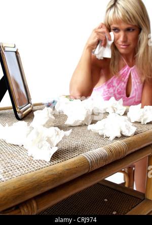 Jeune femme à la recherche de photo dans un cadre en face d'elle sur la table qui est plein de tissus utilisés Banque D'Images