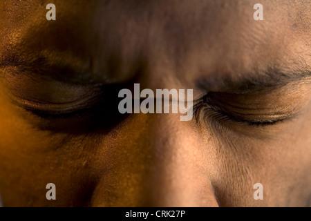 Un jeune homme tire ses yeux fermés. Banque D'Images