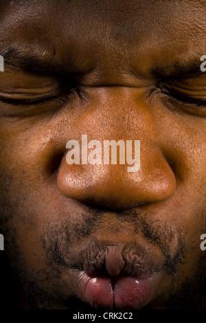 Un jeune homme tire ses yeux fermés, ainsi que serrant ses lèvres hermétiquement fermé. Banque D'Images