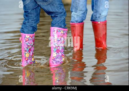 Enfants jouant dans une flaque d'eau, le port de bottes wellington colorés. Banque D'Images