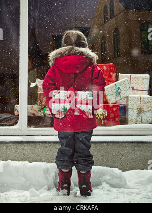 Girl holding Christmas present in snow Banque D'Images