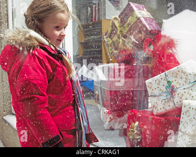 Girl admiring Christmas gifts in snow Banque D'Images
