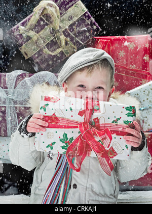 Boy holding Christmas present in snow Banque D'Images