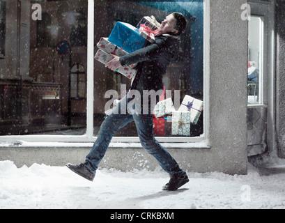 Homme portant des cadeaux de Noël dans la neige Banque D'Images