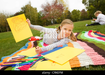 Girl drawing on picnic blanket Banque D'Images