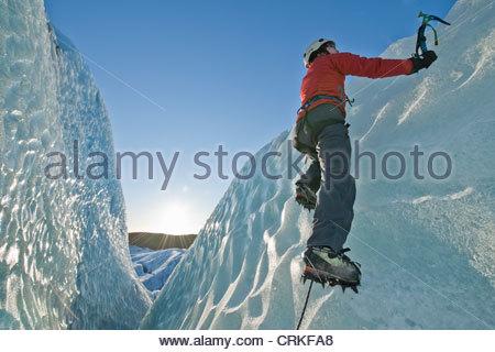 Climber scaling mur glacier Banque D'Images