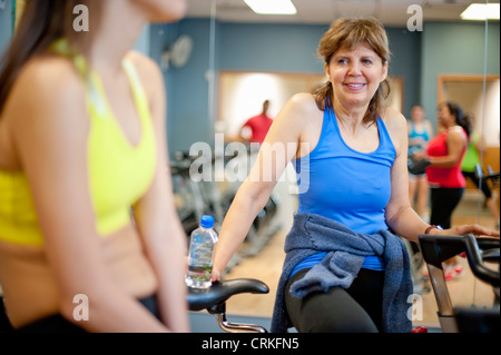 Escalade femme machine spin in gym Banque D'Images