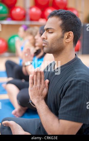 Man practicing yoga in studio Banque D'Images