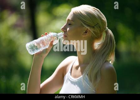 Une jeune blonde boire une bouteille d'eau, Close up Banque D'Images