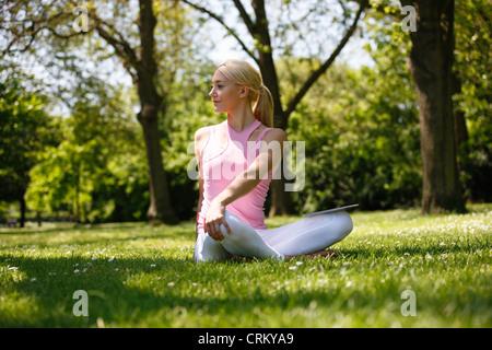 Une jeune femme blonde assise dans l'herbe, stretching Banque D'Images