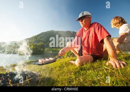 Un couple bénéficiant d'un barbecue sur les rives de Rydal Water dans le Lake District, UK. Banque D'Images
