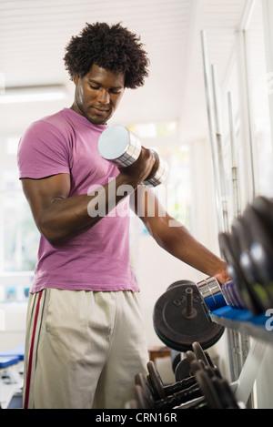 Sport et amusement, young african american male athlete de prendre des poids de l'étagère dans le club de remise Banque D'Images