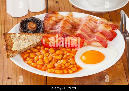 Le petit déjeuner anglais complet sur une vieille table de cuisine en pin. Banque D'Images