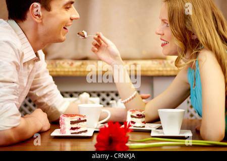 Les jeunes gens assis dans le café et de manger le dessert, fille partage le gâteau avec son petit ami Banque D'Images