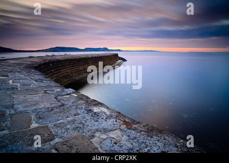 """Lever de soleil sur """"l' Cobb, un mur du port qui permettait à Lyme Regis pour devenir un important port à partir Banque D'Images"""