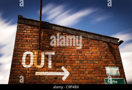 Exit sign painted sur un vieux bâtiment en brique exposer longtemps avec les nuages en mouvement Banque D'Images