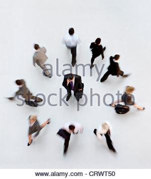 Les gens d'affaires marche loin de businessman talking on cell phone Banque D'Images
