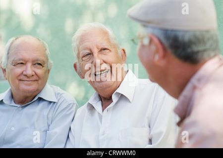 Retraite Active, groupe de trois vieux amis parler et rire sur un banc dans un parc public Banque D'Images