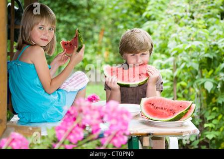 Garçon et fille des pastèques dans le jardin Banque D'Images