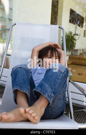 Garçon se détendre dans une chaise longue sur le patio Banque D'Images