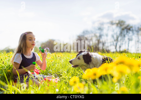 Girl blowing bubbles with dog in field Banque D'Images