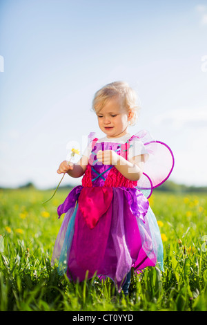 Girl in fairy costume playing in field Banque D'Images