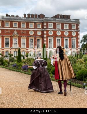 L'homme et la femme à s'habiller en période le jardin privé en face de Christopher Wren's extension de Hampton Court Banque D'Images